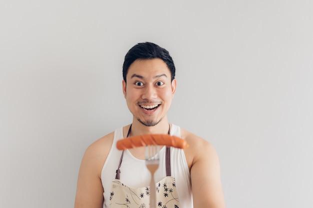 Blij gezicht van de man trots om te eten en worst te koken.