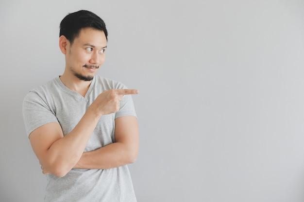 Blij gezicht van de mens in grijs t-shirt met hand punt op lege ruimte.