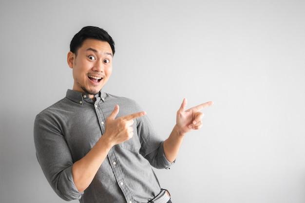 Blij gezicht van grappige goed uitziende man met handteken wijzen.