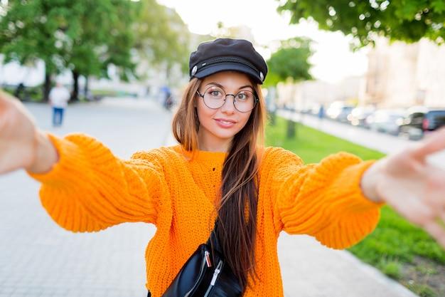 Blij glimlachend donkerbruin meisje in ronde oogglazen en trendy oranje gebreide sweater die zelfportret maken