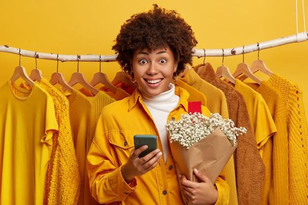 Blij glimlachende afro-amerikaanse dame houdt boeket bloemen en moderne mobiele telefoon, vormt in de buurt van kledingrek opknoping op de achtergrond