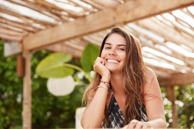 Blij goed uitziende brunette vrouw met vrolijke glimlach in gezellig restaurant, geniet van warm zomerweer, in hoge stemming na spa-procedure
