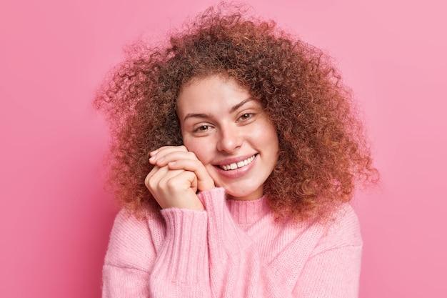 Blij, goed uitziende jonge vrouw met krullend borstelig haar houdt handen in de buurt van gezicht drukt positieve emoties uit, drukt oprechte gevoelens uit tegen roze muur. aangenaam emoties concept