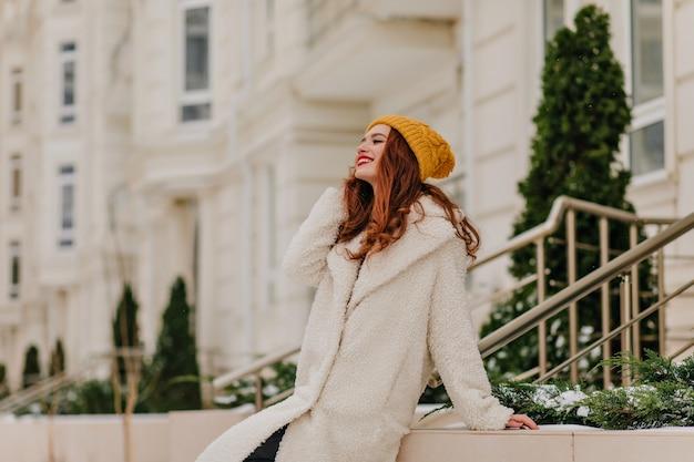 Blij, goedgeklede dame die ontspant in de winter. openluchtportret van vrolijk gembermeisje in lange vacht.