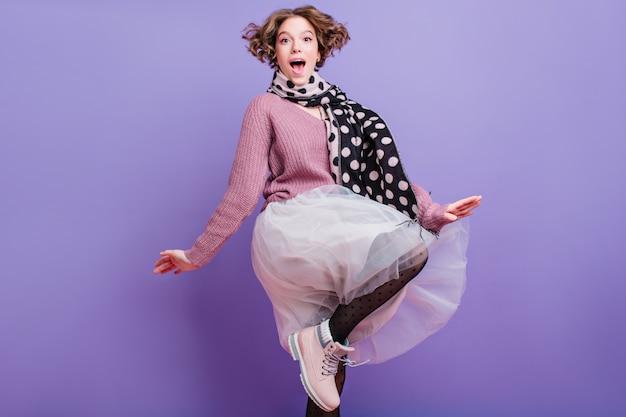 Blij grappig meisje met kort krullend kapsel springen indoor foto van blij jonge vrouw in weelderige rok en sjaal met plezier.