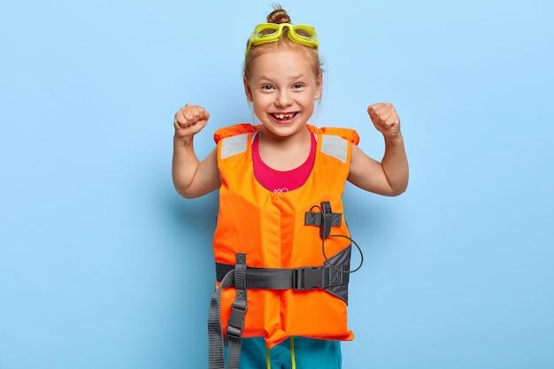 Blij grappig meisje met roodharige gekamd in broodje, heft armen op en toont spieren