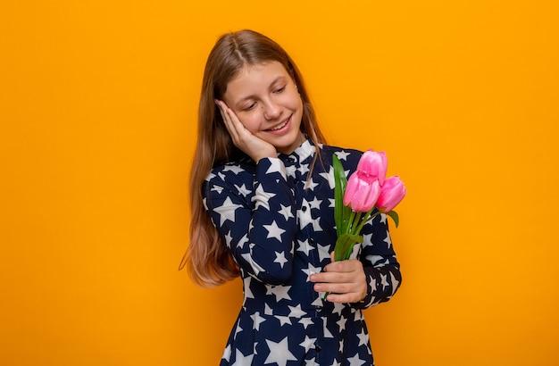 Blij hand op de wang te leggen, mooi klein meisje dat bloemen vasthoudt en bekijkt
