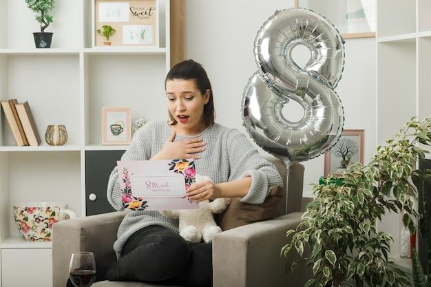 Blij hand op hart mooi meisje op gelukkige vrouwendag te houden en wenskaart te lezen zittend op een fauteuil in de woonkamer