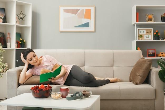Blij hand op het hoofd te leggen jong meisje liggend op de bank achter de salontafel leesboek in de woonkamer