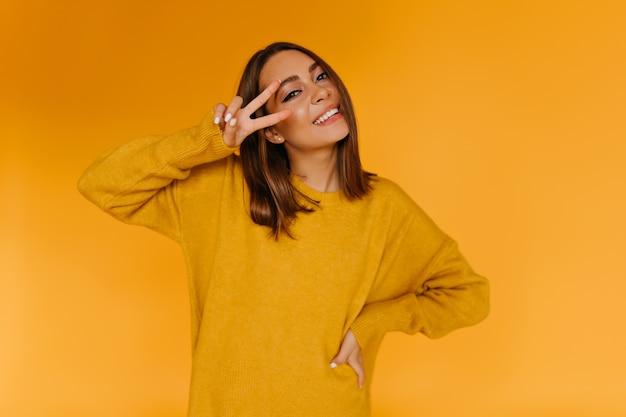 Blij het gebruinde vrouw poseren met vredesteken. fascinerend kaukasisch meisje in gele trui glimlachen.