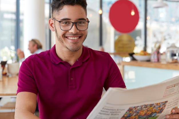 Blij hipster-man draagt een bril, heeft een zachte glimlach op het gezicht, leest in de vrije tijd goed nieuws in de krant, wacht op bestelling in cafetaria, dol op pers. knappe man geïnteresseerd in nieuwe evenementen van land