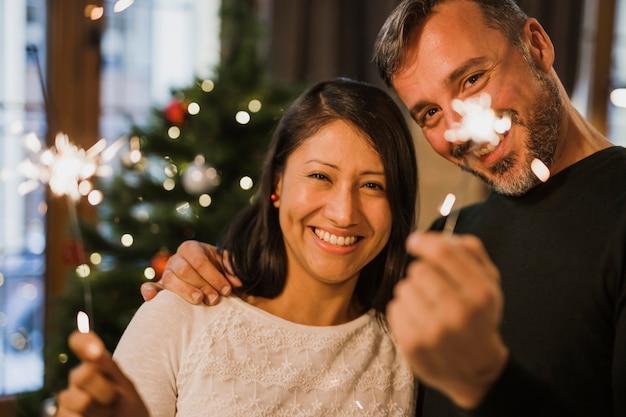 Blij hoger paar bij de kerstboom met lichten