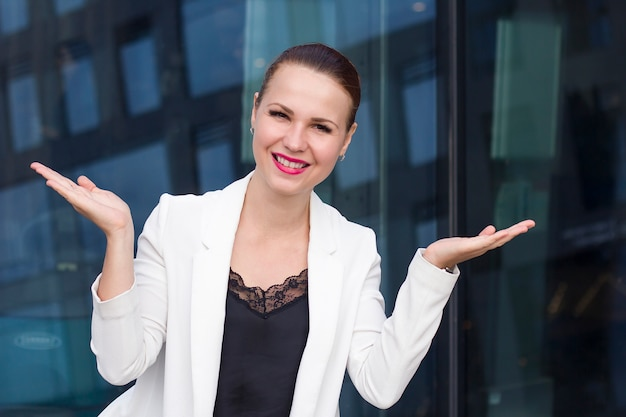Blij je te zien! aangenaam kennis te maken! mooie gelukkige jonge zakenvrouw in formeel weer, pak maken van een schaal met haar armen wijd open, camera kijken en glimlachen. welkomstbord, gebaar.