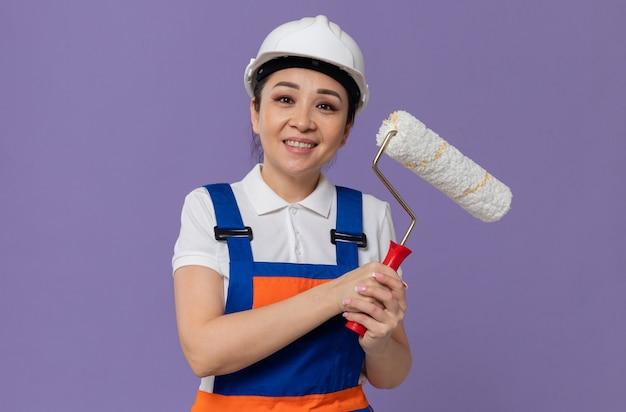 Blij jong aziatisch bouwersmeisje met witte veiligheidshelm die verfroller houdt