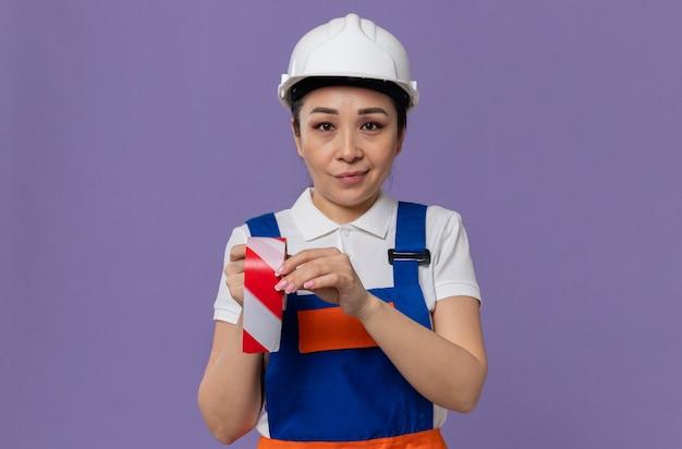 Blij jong aziatisch bouwersmeisje met witte veiligheidshelm die waarschuwingsband houdt