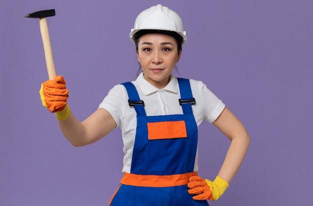 Blij jong aziatisch bouwersmeisje met witte veiligheidshelm en handschoenen die hamer houden