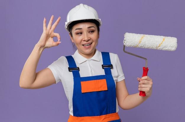 Blij jong aziatisch bouwmeisje met een witte veiligheidshelm die een verfroller vasthoudt en een ok teken gebaart