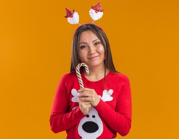 Blij jong aziatisch meisje dat de hoepel van het kerstmishaar met sweater draagt die kerstmissuikergoed houdt dat op oranje muur wordt geïsoleerd