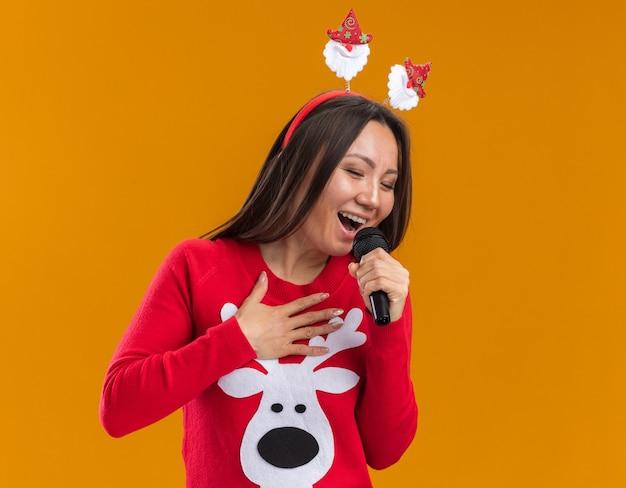 Blij jong aziatisch meisje die de hoepel van het kerstmishaar met sweater dragen zingt op microfoon die op oranje muur wordt geïsoleerd