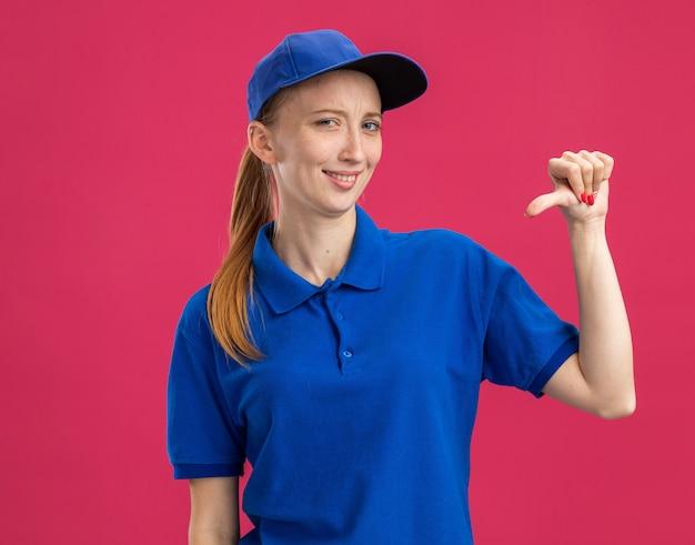 Blij jong bezorgmeisje in blauw uniform en pet glimlachend zelfverzekerd wijzend naar zichzelf terwijl ze over roze muur staat