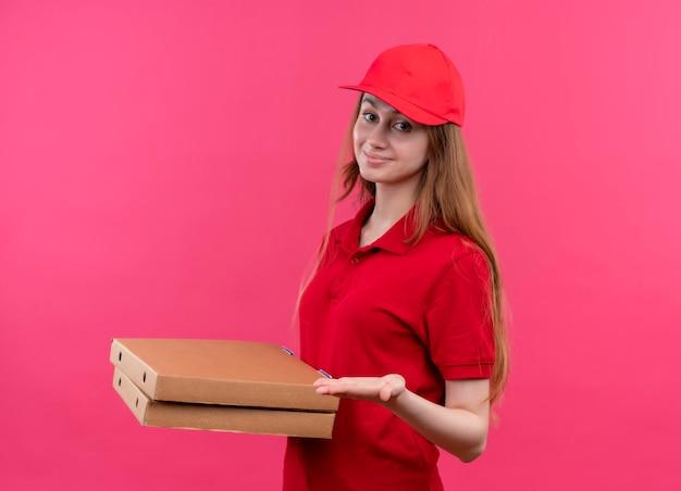 Blij jong bezorgmeisje in rode uniforme bedrijfspakketten en lege hand tonen op geïsoleerde roze ruimte