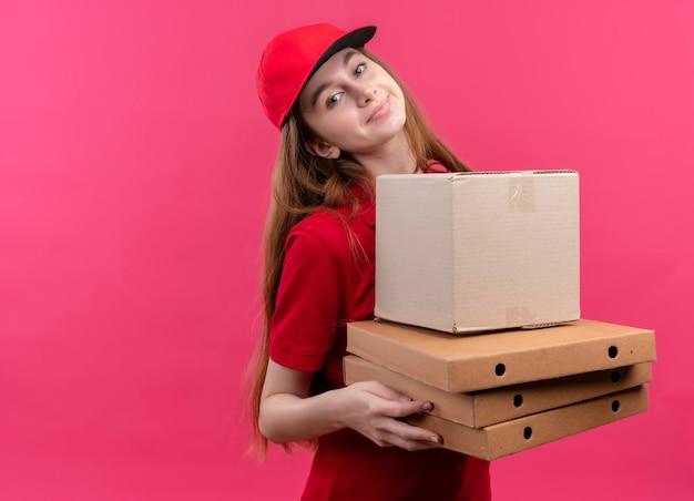 Blij jong bezorgmeisje in rode uniforme holdingsdoos en pakketten op geïsoleerde roze ruimte met exemplaarruimte