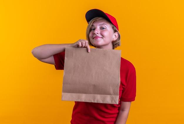 Blij jong bezorgmeisje in uniform met dop met papieren voedselzak geïsoleerd op oranje muur