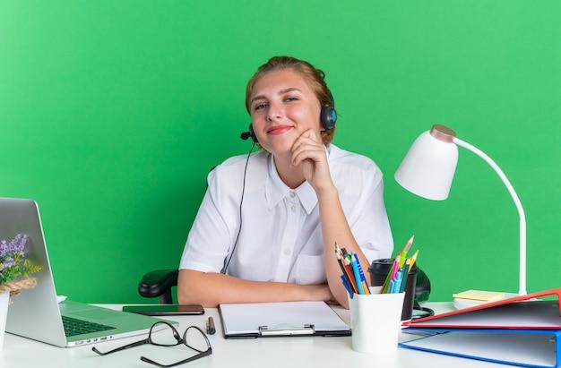 Blij jong blond callcentermeisje met een hoofdtelefoon die aan het bureau zit met uitrustingsstukken die de hand op de kin houden