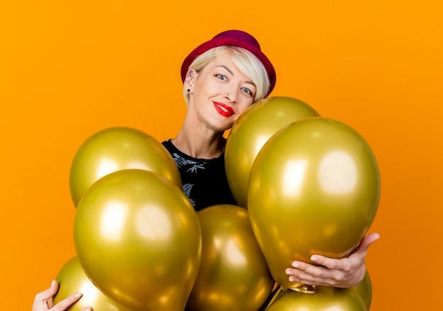 Blij jong blond feestmeisje dat feestmuts draagt die zich achter ballons bevindt die hen grijpen die camera bekijken die op oranje achtergrond wordt geïsoleerd