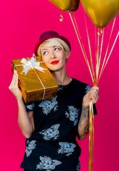 Blij jong blond feestmeisje die de doos van de de holdingsgift van de partijhoed op schouder en ballons dragen die kant bekijken die op karmozijnrode achtergrond wordt geïsoleerd Gratis Foto