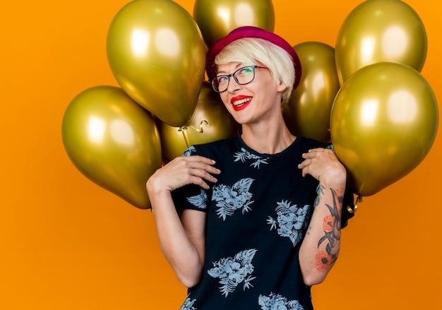 Blij jong blond feestmeisje die feestmuts en bril dragen die zich voor ballons bevinden die kant wat betreft schouders bekijken die op oranje achtergrond worden geïsoleerd