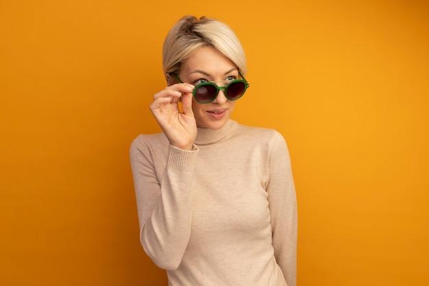 Blij jong blond meisje dat een zonnebril draagt en grijpt die naar de zijkant kijkt die op een oranje muur met kopieerruimte is geïsoleerd