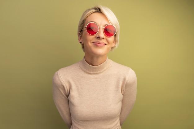 Blij jong blond meisje met een zonnebril die de handen achter de rug houdt