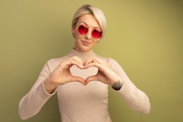 Blij jong blond meisje met een zonnebril die hartteken doet