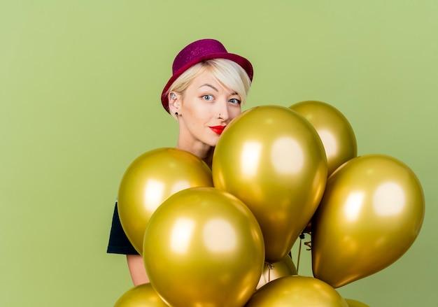 Blij jong blond partijmeisje die partijhoed dragen die zich achter ballons bevinden die camera bekijken die op olijfgroene achtergrond met exemplaarruimte wordt geïsoleerd