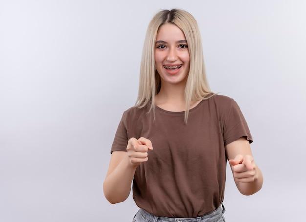 Blij jong blondemeisje in tandsteunen die u gebaar op geïsoleerde witte ruimte met exemplaarruimte doen