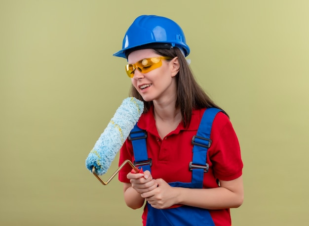 Blij jong bouwersmeisje met blauwe veiligheidshelm en met veiligheidsbril houdt verfroller met beide handen op geïsoleerde groene achtergrond