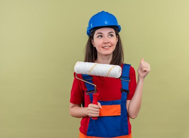 Blij jong bouwersmeisje met blauwe veiligheidshelm houdt verfroller en heft vuist op geïsoleerde groene achtergrond met exemplaarruimte