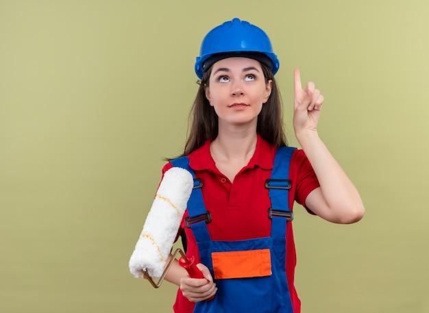 Blij jong bouwersmeisje met blauwe veiligheidshelm houdt verfroller en wijst op geïsoleerde groene achtergrond met exemplaarruimte