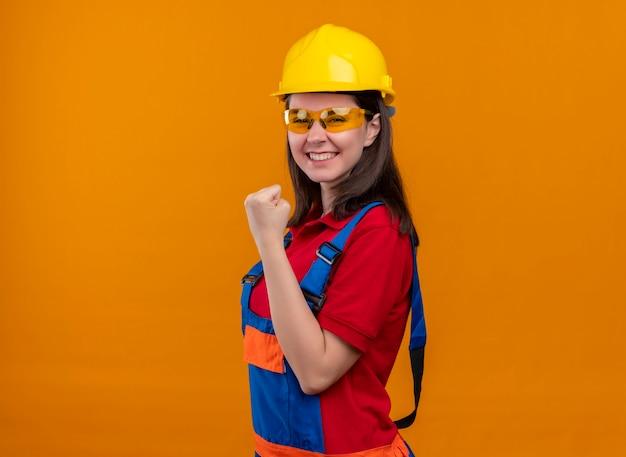 Blij jong bouwersmeisje met veiligheidsbril heft vuist omhoog en staat zijwaarts op geïsoleerde oranje achtergrond met exemplaarruimte