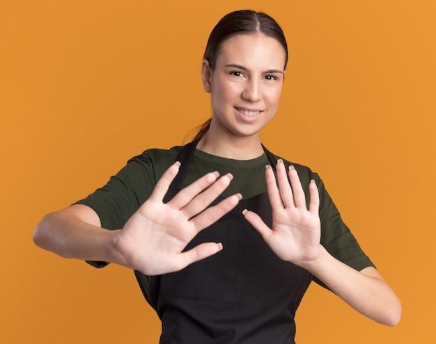 Blij jong brunette kappersmeisje in uniform houdt handen open