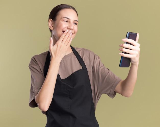 Blij jong brunette kappersmeisje in uniform legt hand op mond houden en kijken naar telefoon geïsoleerd op olijfgroene muur met kopieerruimte