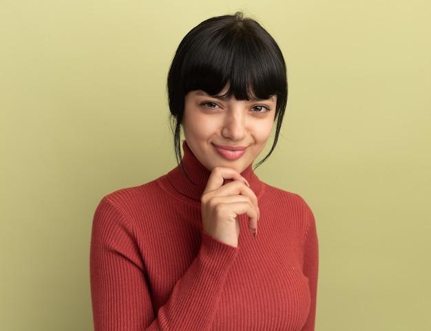Blij jong brunette kaukasisch meisje legt hand op kin en kijkt naar camera