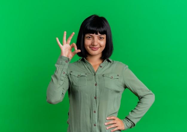 Blij jong brunette kaukasisch meisje legt hand op taille gebaren ok handteken geïsoleerd op groene achtergrond met kopie ruimte