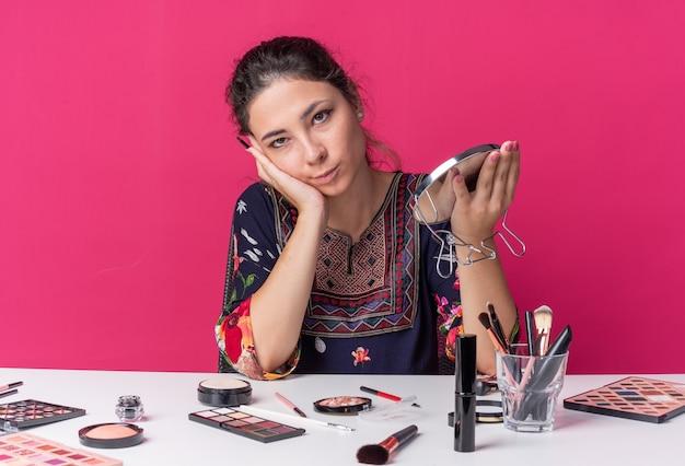 Blij jong brunette meisje zittend aan tafel met make-up tools met make-upborstel en spiegel