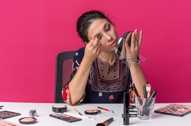 Blij jong brunette meisje zittend aan tafel met oogschaduw toe te passen met make-up borstel houden en kijken naar spiegel geïsoleerd op roze muur met kopie ruimte