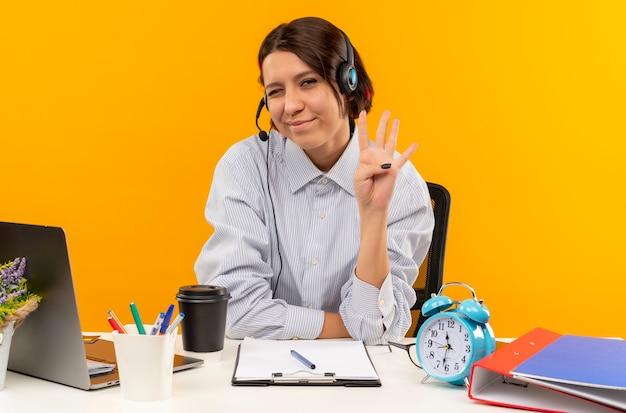 Blij jong call centreermeisje die hoofdtelefoonszitting bij bureau dragen die en vier met hand tonen die op oranje achtergrond wordt geïsoleerd