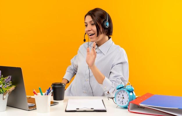 Blij jong call centreermeisje die hoofdtelefoonszitting bij bureau dragen die laptop bekijken die op oranje wordt geïsoleerd