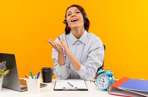 Blij jong call centreermeisje die hoofdtelefoonszitting dragen bij bureau klappen geïsoleerd op oranje