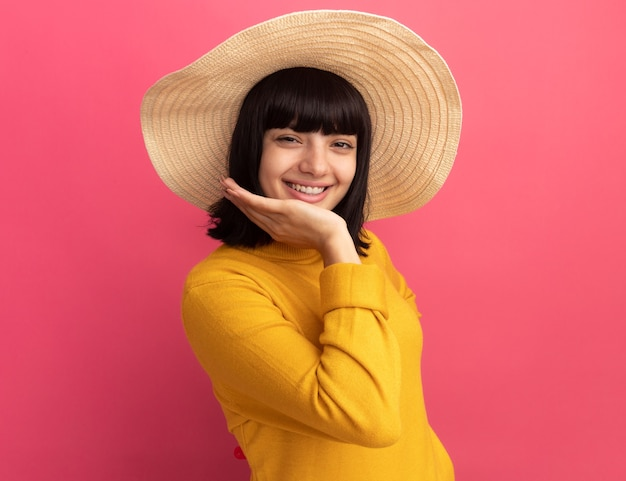 Blij jong donkerbruin kaukasisch meisje dat strandhoed draagt legt hand op kin en bekijkt camera op roze